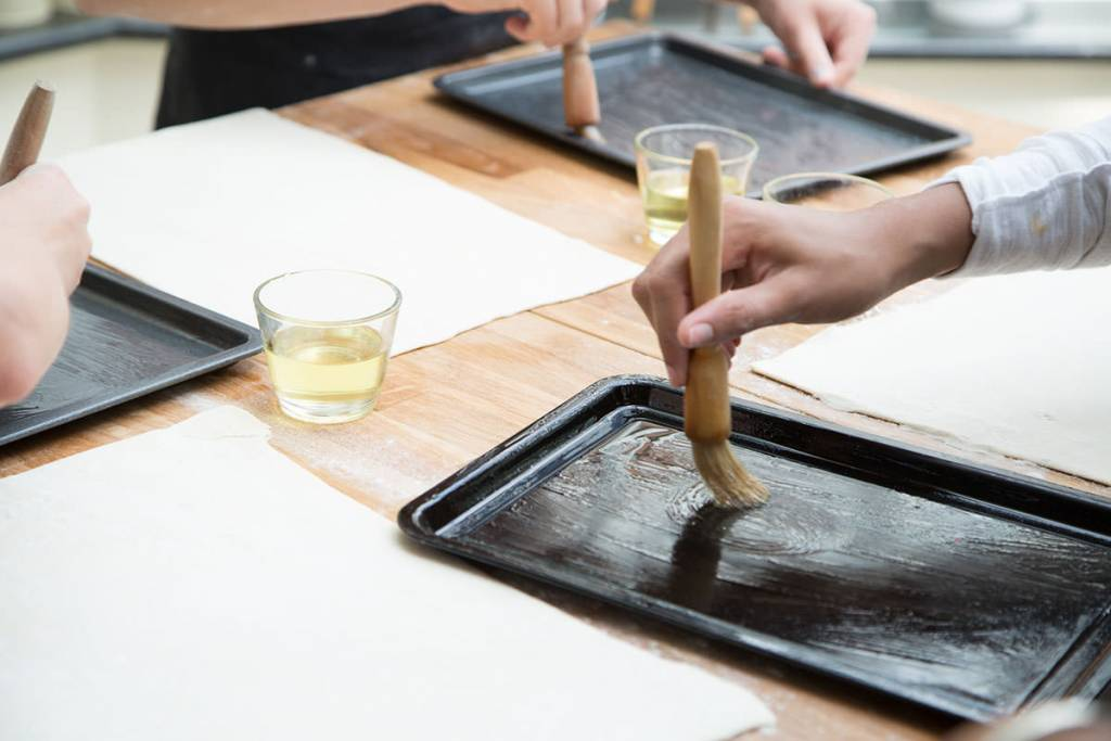 brushing a baking tray with oil
